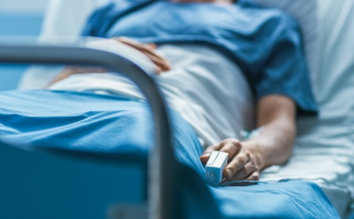 A patient lies in a hospital bed with a blood pressure monitor on their finger.