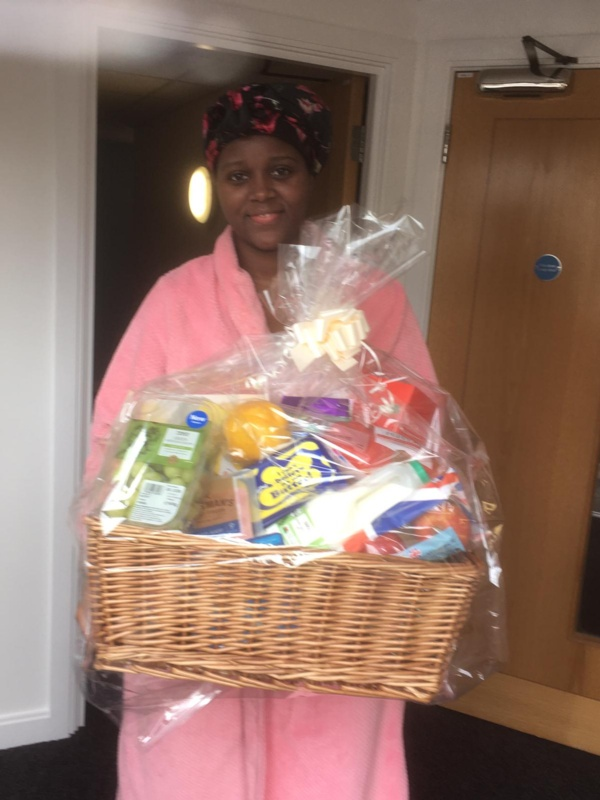 Mum pictured holding a hamper and smiling at the camera.