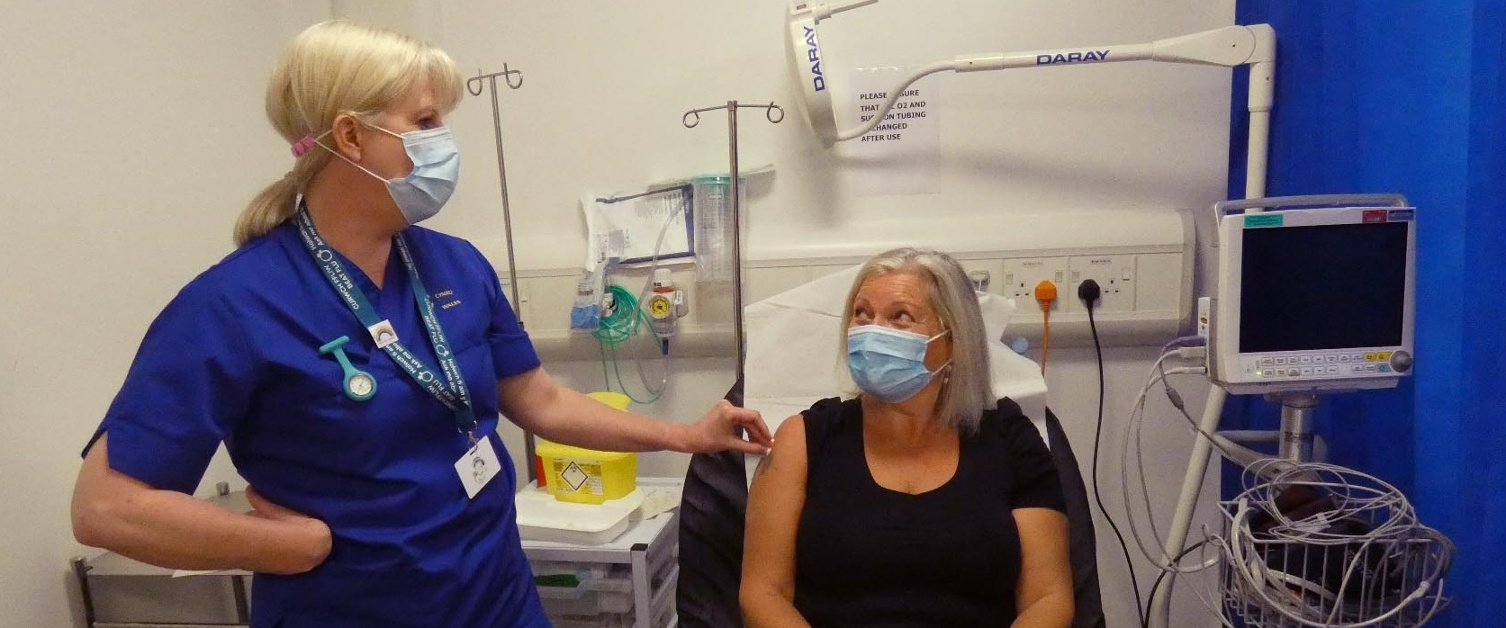 Nurse Cath Courts standing next to Alison Holland lying on trolley.