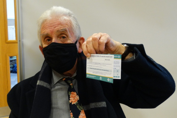 Image shows a man wearing a face mask holding up his vaccination card.