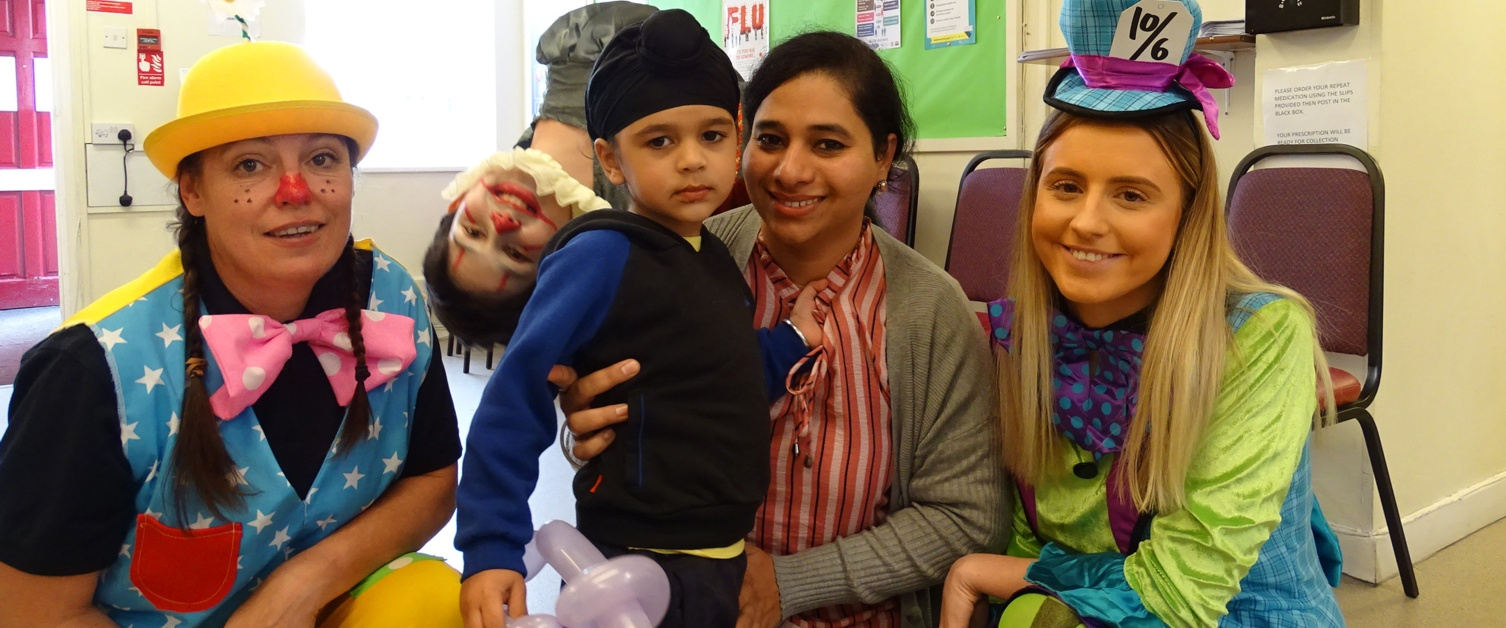 Surgery staff in fancy dress with a smiling mum and son