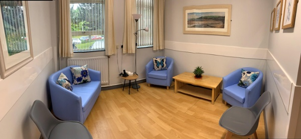 Hospital quiet room with blue sofa and chairs and light soft furnishings