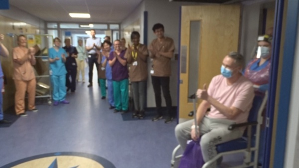 Image shows patient David Courtney-Williams giving the thumbs up to clapping staff.