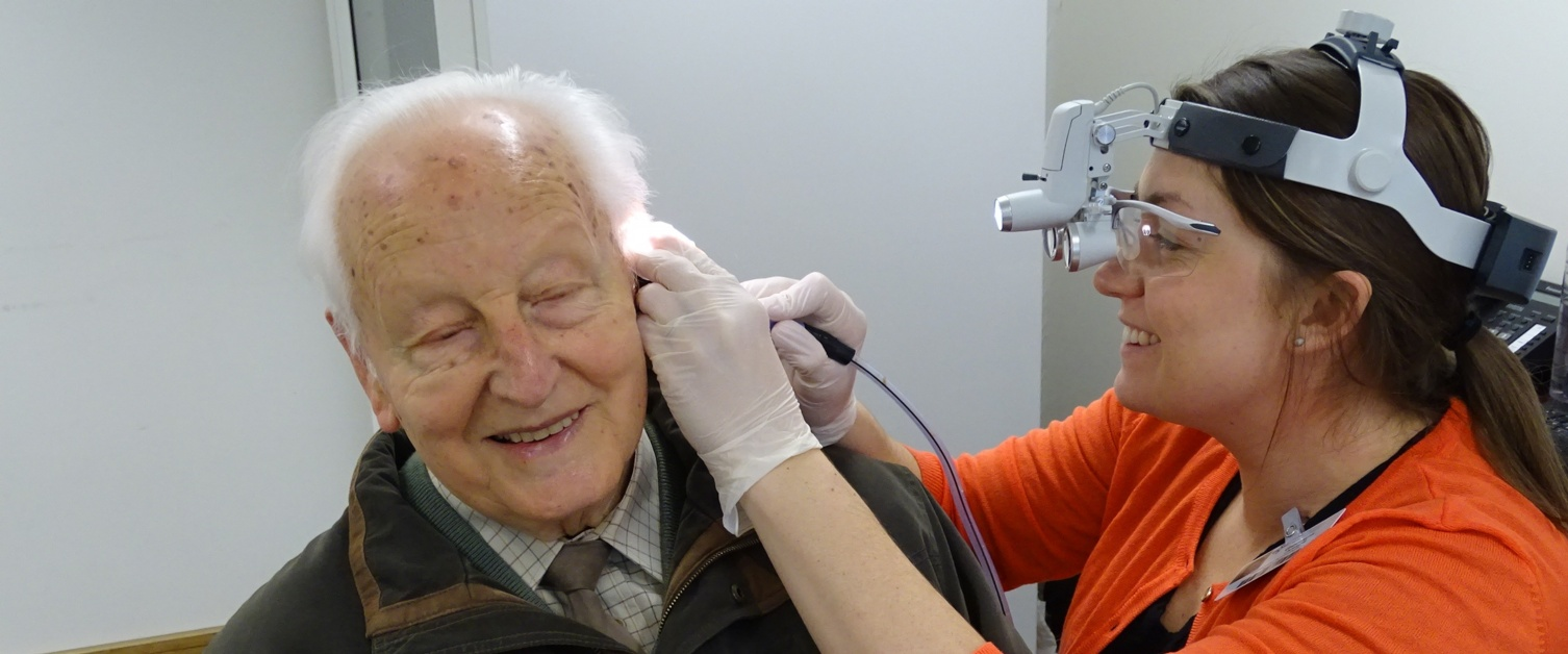 An audiologist checking a patient's ears