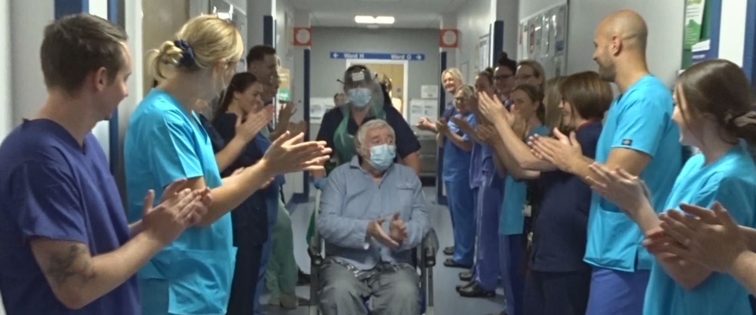 Danny Egan, in a wheelchair, applauds staff who are clapping him