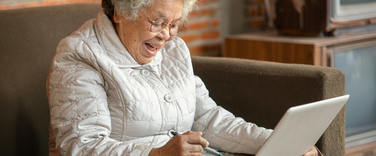 A pensioner sits on a sofa with a laptop on her lap. She is smiling.