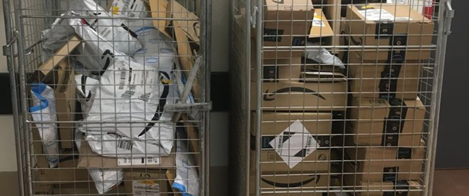 Image shows two metal cages full of Amazon parcels.
