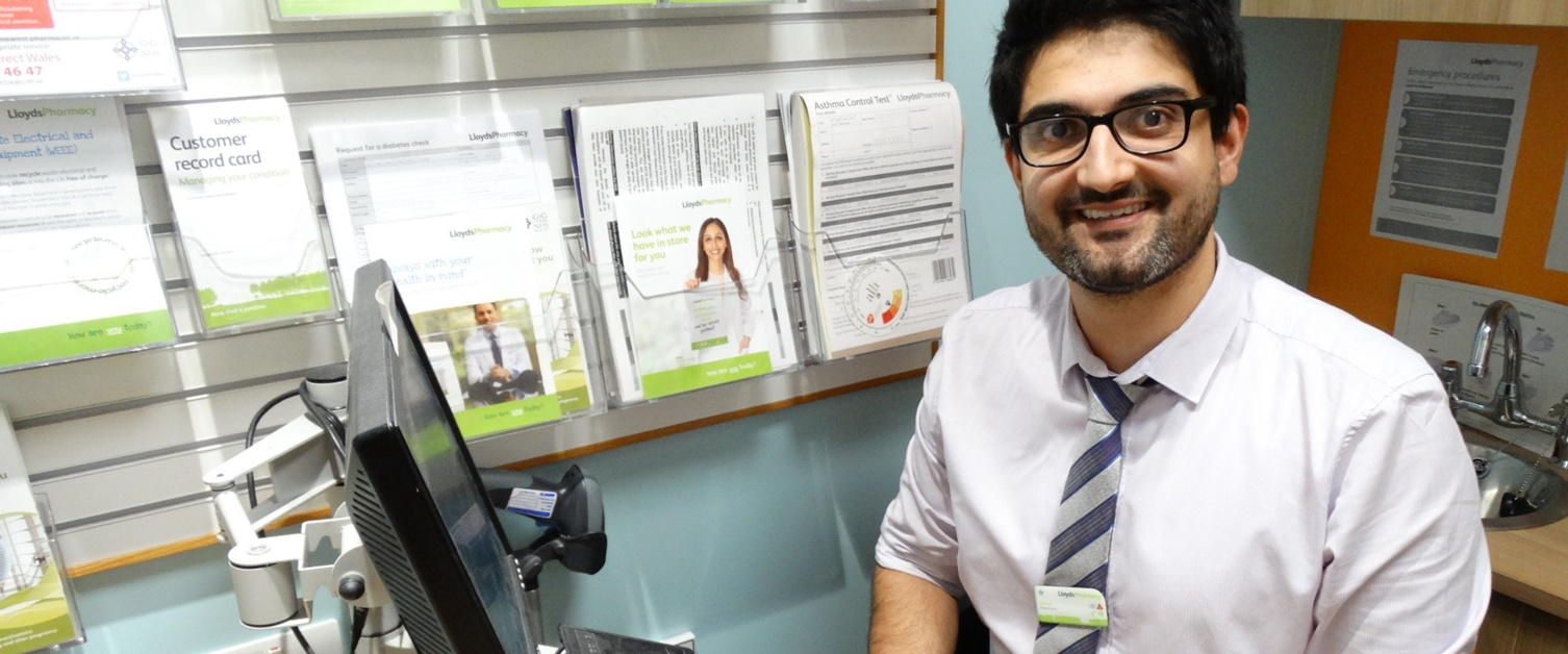 A picture of pharmacist Umar Hussain at his desk