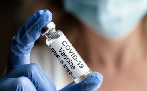 A gloved hand holds a vial marked COVID vaccine.