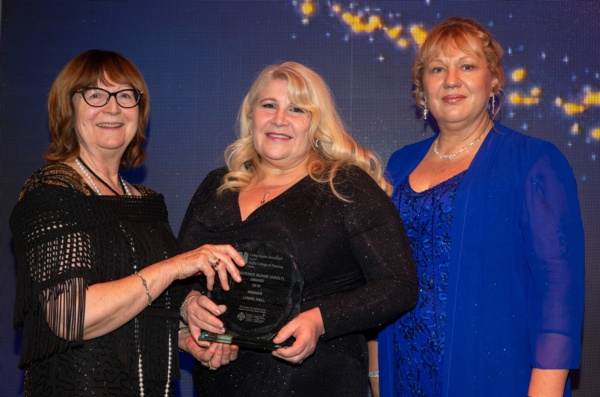 Lynne Hall stands with two other ladies as she holds her RCN award.