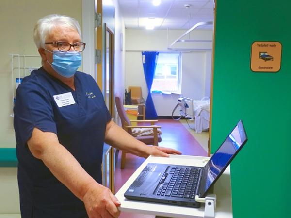 Nurse in a hospital ward using a laptop