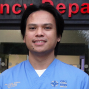 In this profile image, a man wearing pale blue scrubs stands in front of the emergency department entranceway at Morriston Hospital.