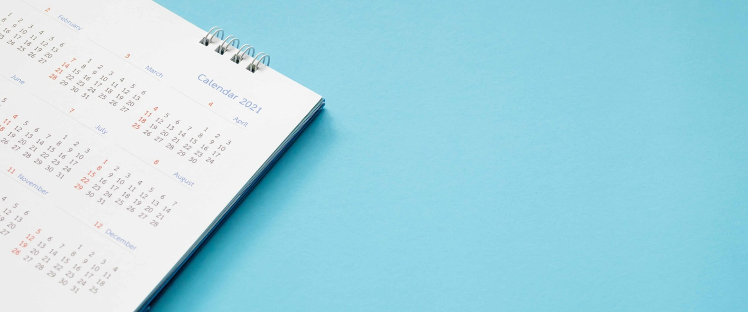 Image shows a paper calendar for 2021 on a blue background.