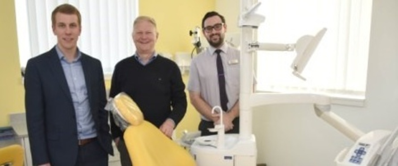 Three male staff members from a dental practice in Swansea stood around a dental chair.