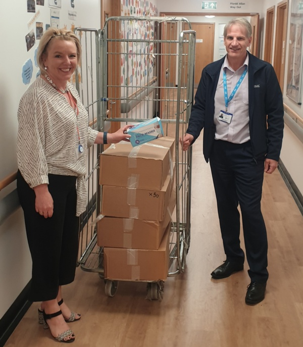 Image shows Deb Lewis and Mark Parsons next to a metal cage containing boxes of PPE.