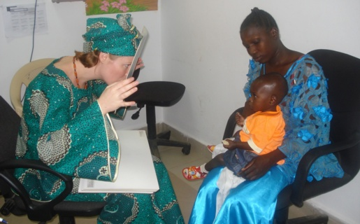 An image of a young person being held by his mother whilst having his eyes tested by a Orthoptist in Gambia