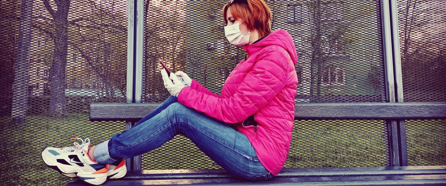 Lady sitting on a bench typing on her phone
