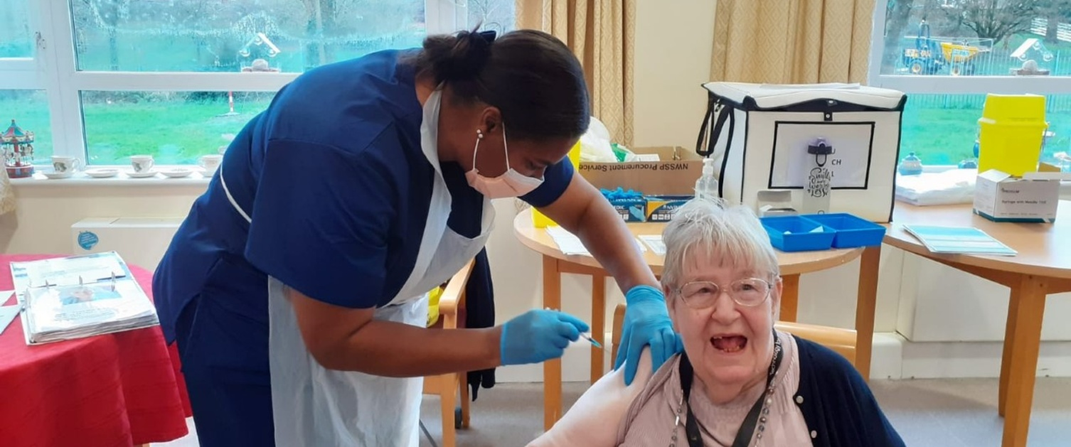 Elderly lady receiving her COVID-19 vaccination