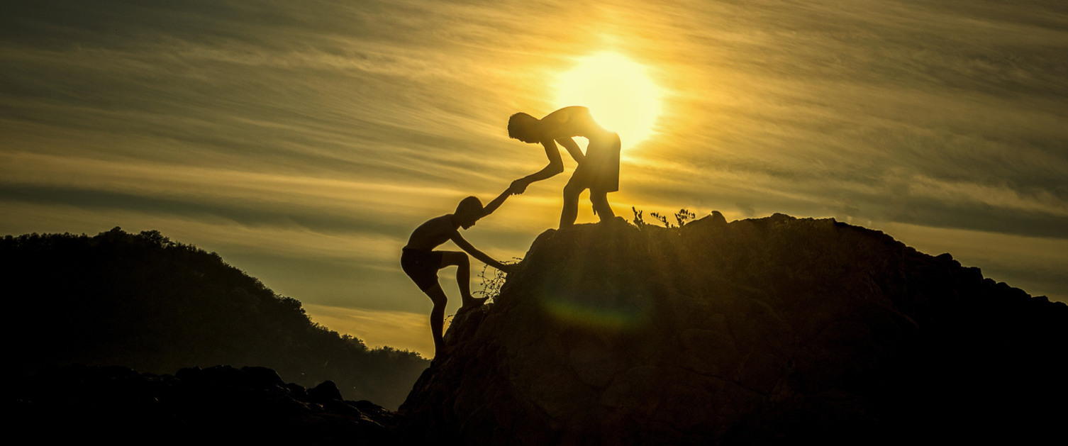 A person helps another climb a hill while the sun sets in the background