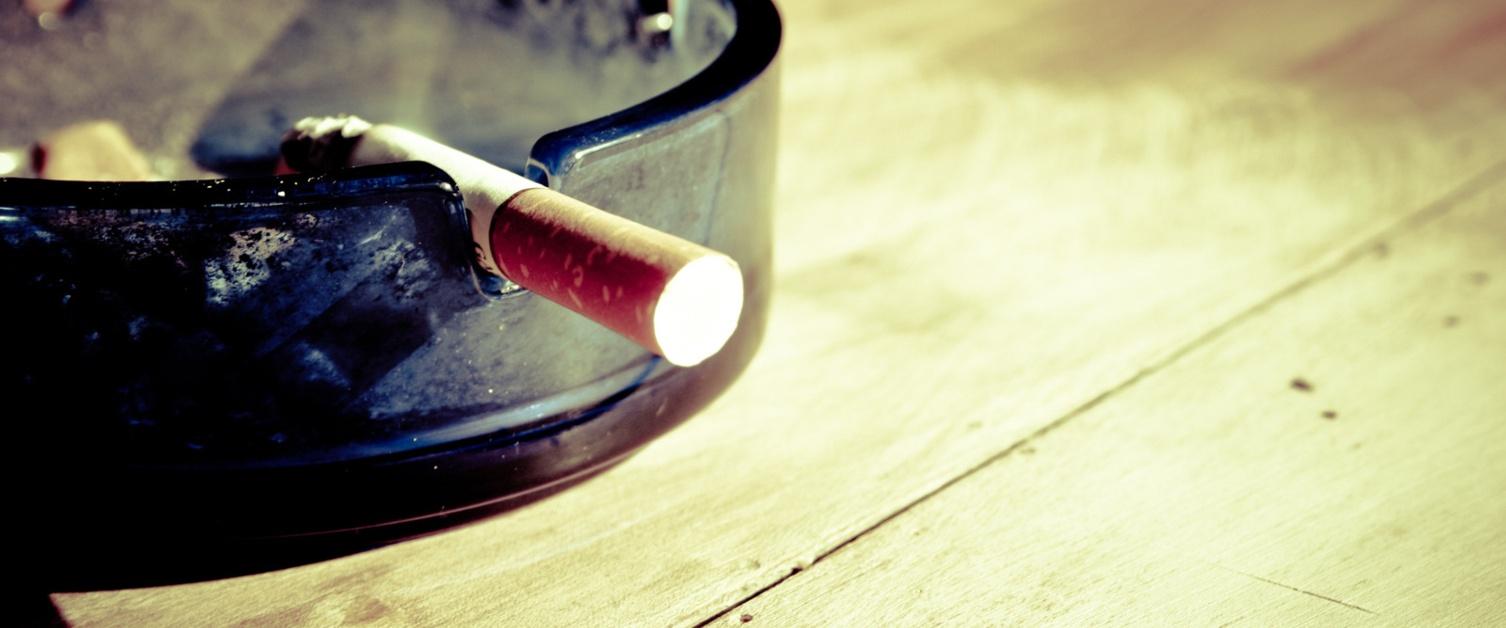 Lit cigarette in ash tray