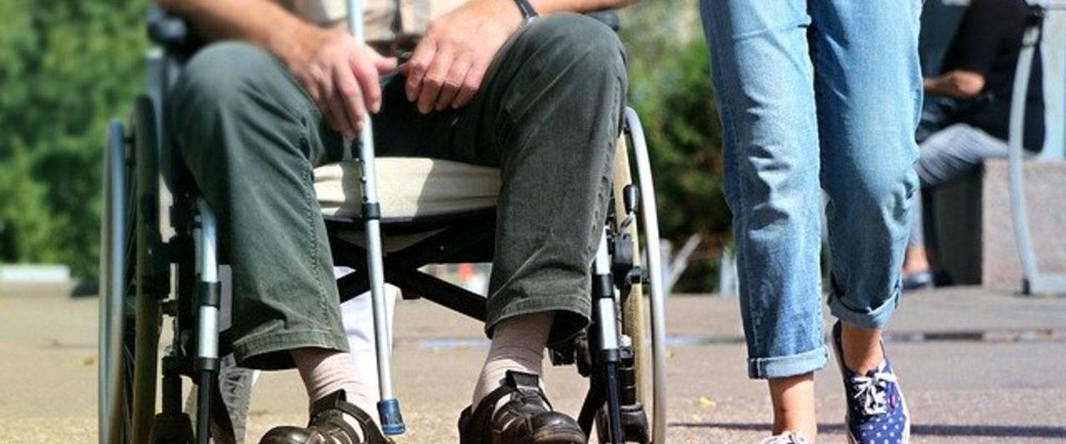 Person walking alongside someone in a wheelchair
