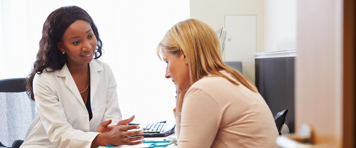 An image of a GP speaking to a female patient in a consulting room