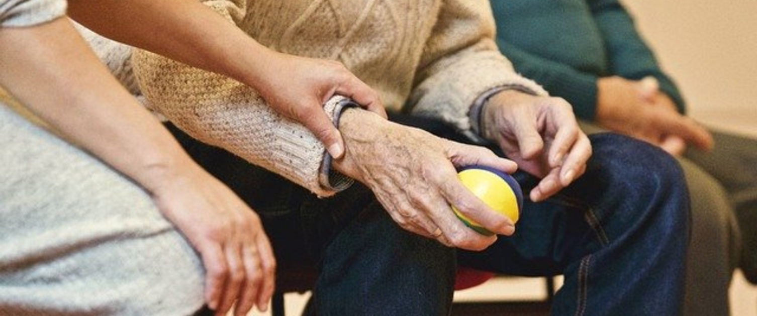 Elderly man holding a ball sat next to a younger woman