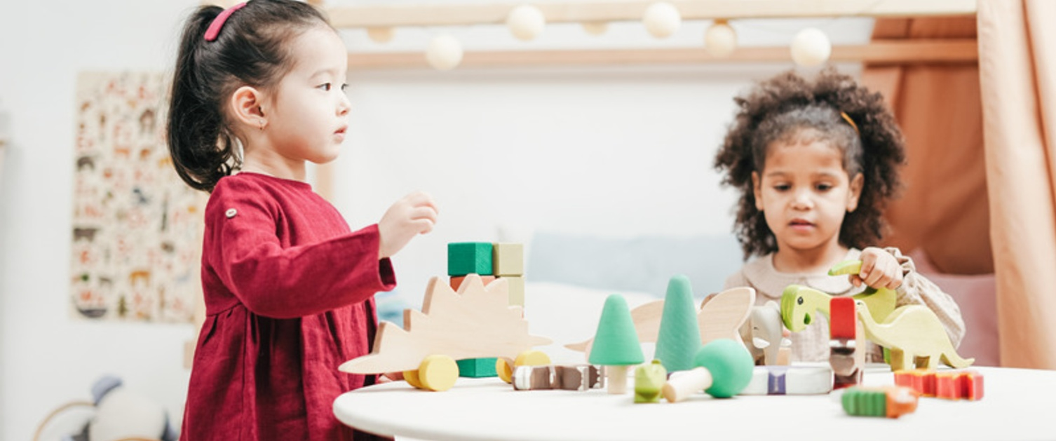 Two children playing with wooden blocks