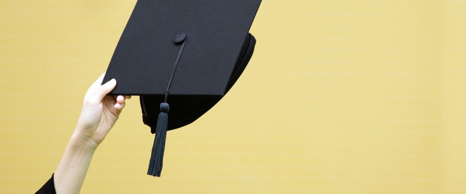 Graduate cap on yellow background