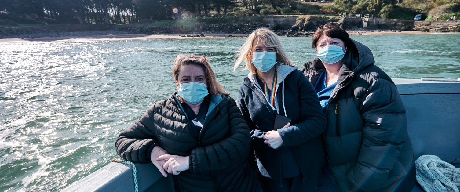 3 nurses on a boat to Caldey Island to deliver the second round of vaccines