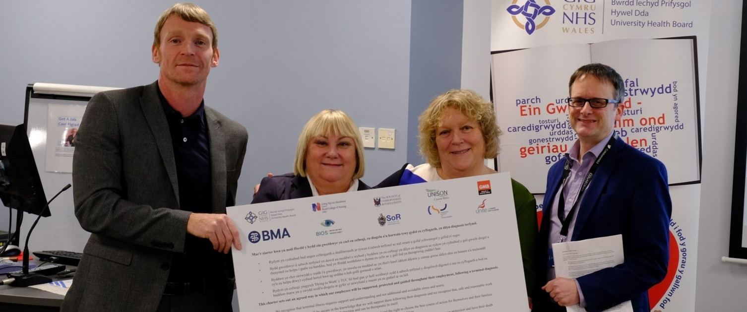 Employee's holding signed Dying to Work Charter