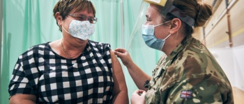 Lady receiving her vaccine from a member of the armed forces