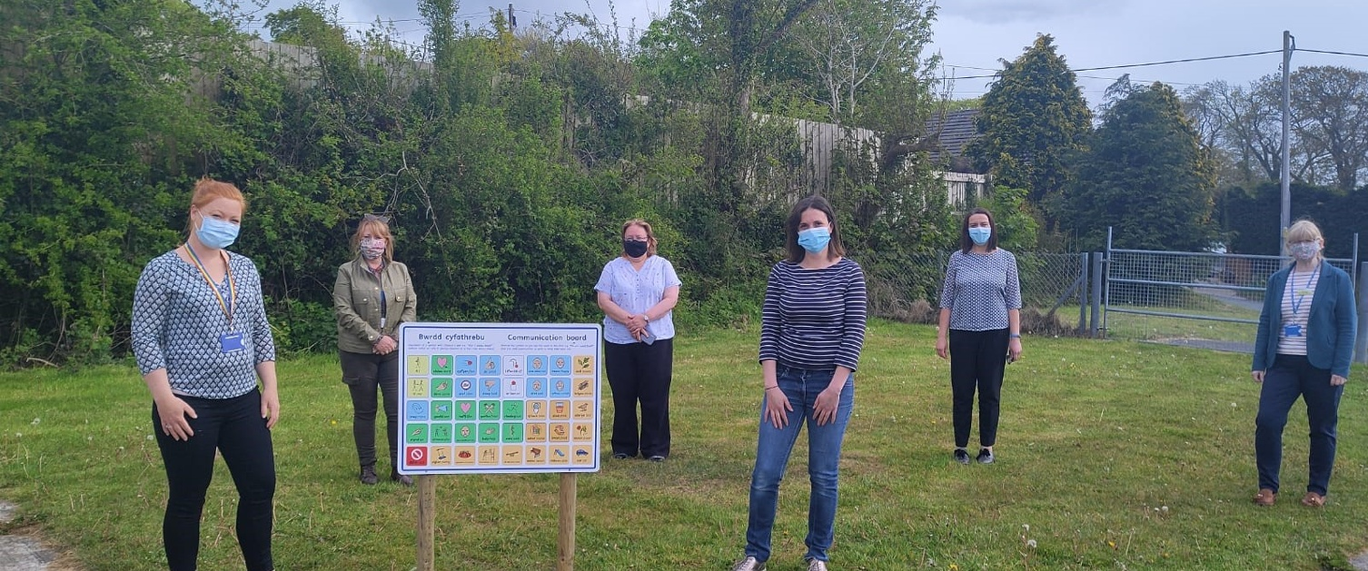 Group of adults standing around new communication board