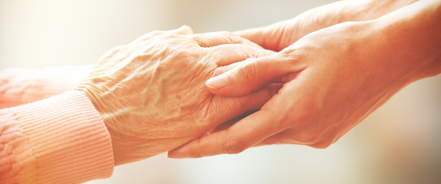 Elderly and younger person holding hands