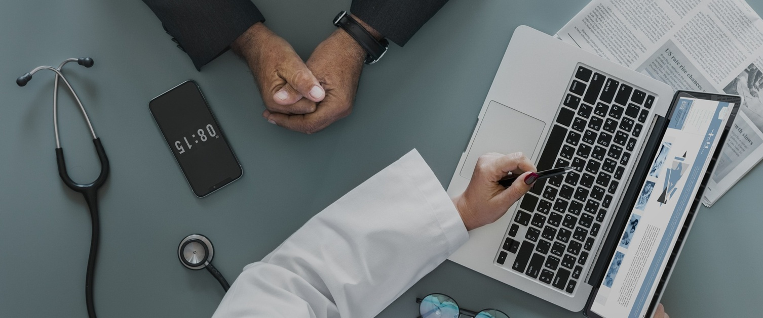 Top-view of doctor pointing to a laptop