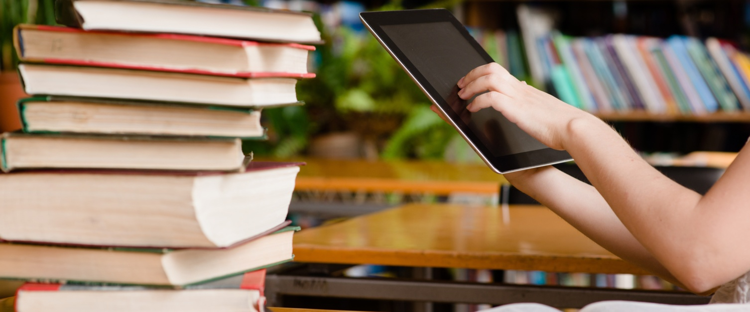 Hands using tablet in library