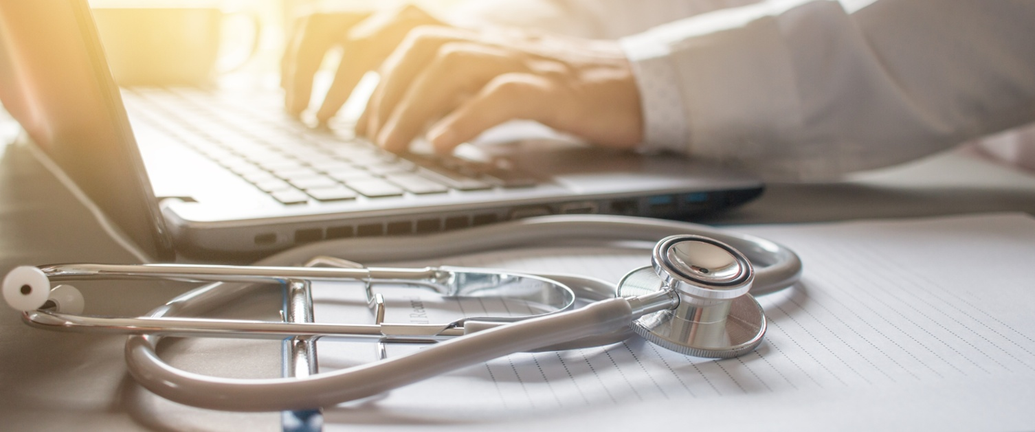 A doctor using a laptop and a stethoscope in the photo