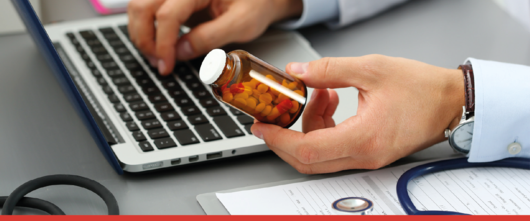 Man looking on the pharmacy database<br>