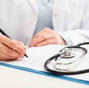 young woman with stethoscope writing prescribing report