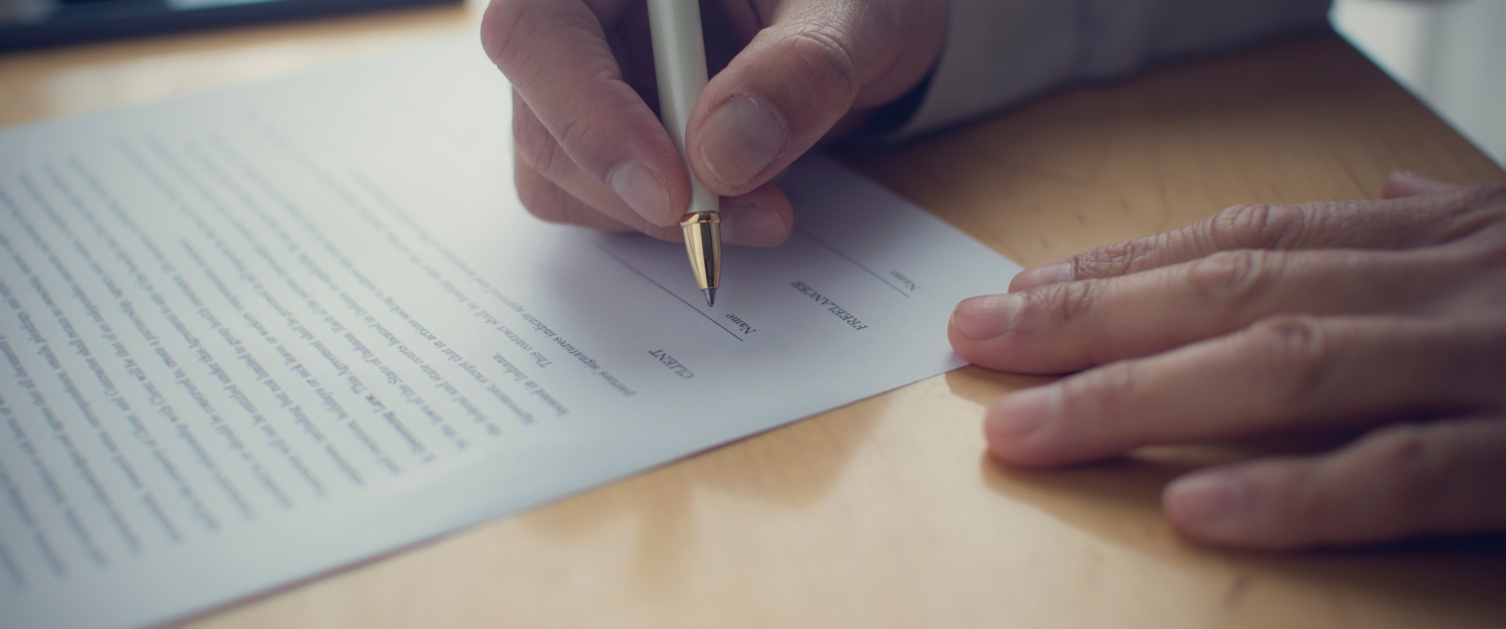 A person signing a document. Hand holding a pen and signing