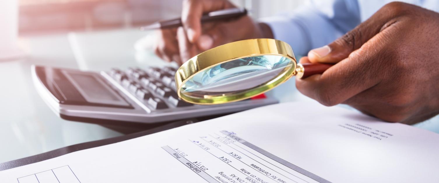 Person examining a document with a magnifying glass / Person yn archwilio dogfen gyda chwyddwydr