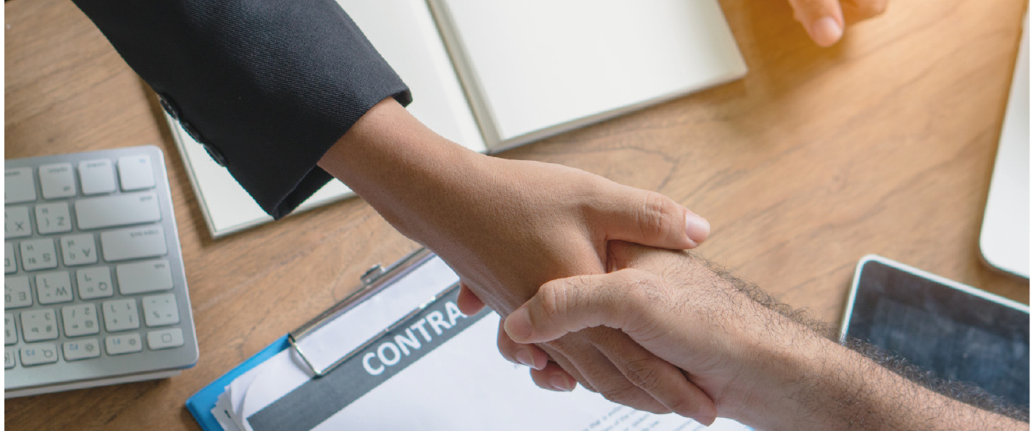Shaking hands across a desk