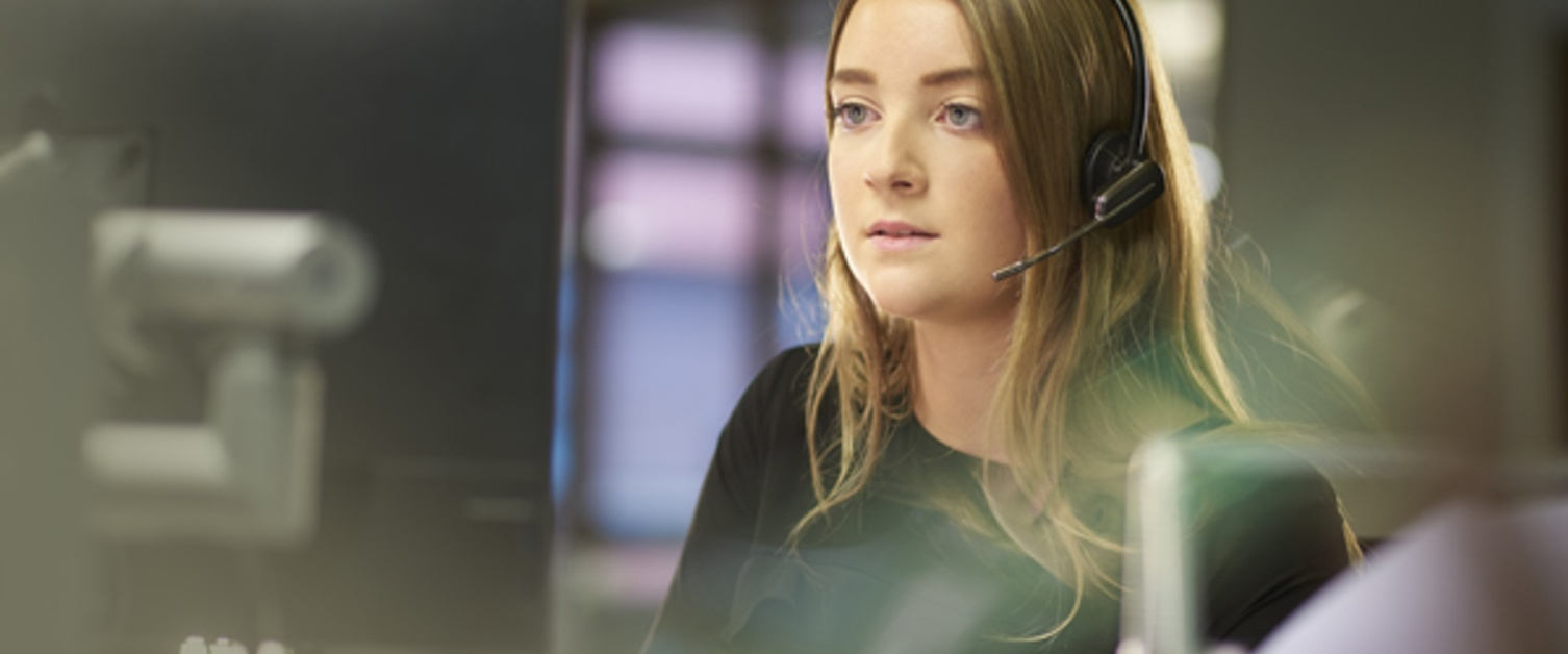 The image shows a member of staff wearing a headset working in an office responding to calls.