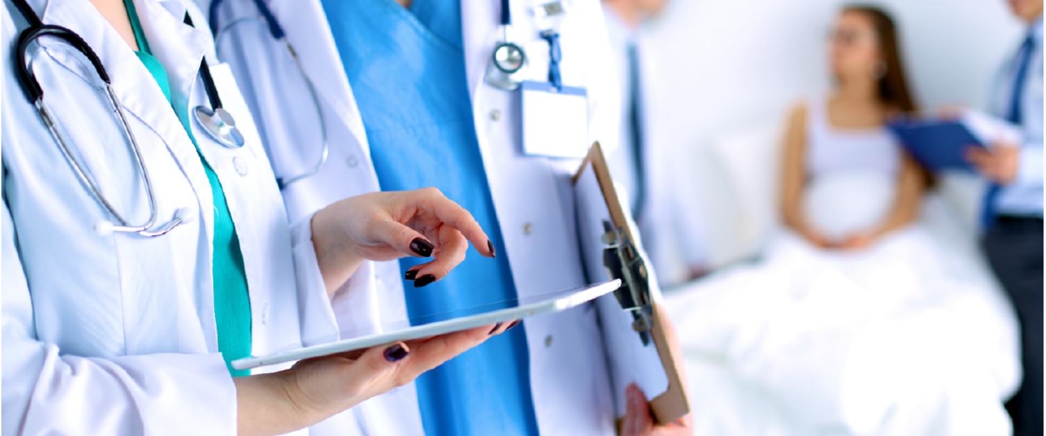 The image shows several clinicians reviewing patient notes