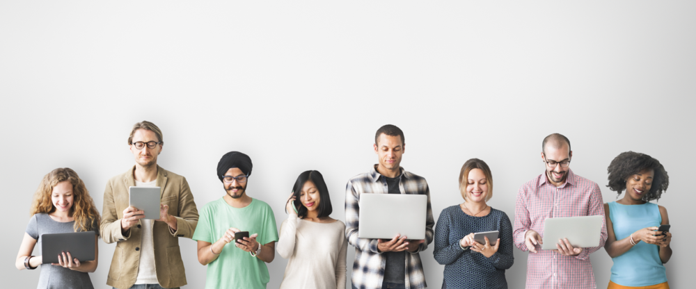 The image shows a group of individuals of various ages and ethnicities using different electronic devices